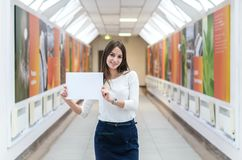 The dark-haired student girl on the campus is holding a blank sheet of paper royalty free stock photos