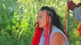A dark-haired stylist weaves braids with red threads to a young woman. The average plan stock video