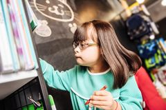 Dark-haired sunny child drawing something on the blackboard stock photos