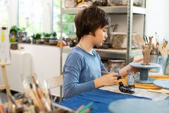 Dark-haired talented boy sculpting figures with clay. Figures with clay. Dark-haired talented boy sculpting figures with clay while attending art school royalty free stock photo