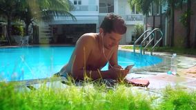 Guy surfs internet over smartphone by pool barrier. Dark-haired tanned guy surfs internet on smartphone leaning on resort hotel swimming pool barrier stock video