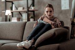 Dark-haired teenage girl sitting on sofa feeling awful bursting into tears. Feeling awful. Dark-haired teenage girl sitting on sofa feeling awful bursting into stock photography