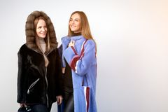 Dark-haired woman in a blue fur coat. Two young beautiful women in black and naked fur coats from natural fur mink posing on white isolated background Stock Photography