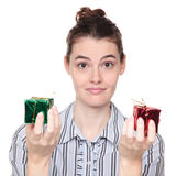 Dark haired woman choosing between Christmas gifts Royalty Free Stock Photos