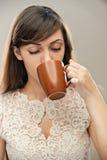 Dark-haired woman drinking tea Stock Photos