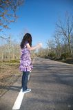 Dark-haired woman hitchhiking Stock Image