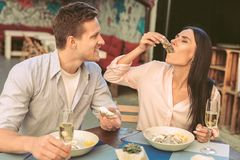 Dark-haired woman in light blouse sipping fresh oyster directly from shell. Girl taking oyster. Dark-haired women in light blouse sipping fresh oyster directly stock photography