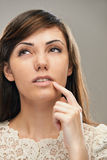 Dark-haired woman looking thoughtfully up Stock Image