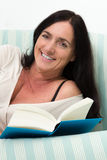 Dark haired woman lying on couch and reading a book Royalty Free Stock Photos