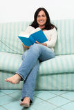 Dark haired woman lying on couch and reading a book Royalty Free Stock Images