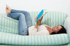 Dark haired woman lying on couch and reading a book Stock Photo