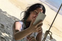 A dark-haired woman photographs herself in a tropical beach Stock Photo