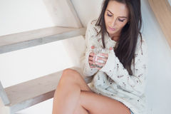 Dark-haired woman is sitting at the stairs in cozy. Home atmosphere drinking coffee Royalty Free Stock Image