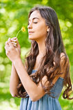 Dark-haired woman smells dandelion Royalty Free Stock Photo