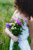Dark haired woman in summer dress holding bunch of colorful flow Royalty Free Stock Photography