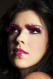Dark haired woman wearing fantasy pink makeup Royalty Free Stock Images
