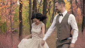 Happy couple running in autumn park and smiling, slow motion. A dark-haired woman in a white dress and a bearded man in a suit run in an autumn park stock video