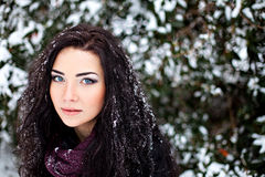 Dark-haired woman in winter snowy forest Royalty Free Stock Image