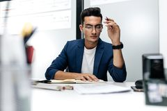 Dark-haired young architect in glasses and in a blue jacket is working with documents on the desk in the office stock images