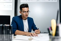 Dark-haired young architect in glasses and in a blue jacket is working with documents on the desk in the office royalty free stock photography