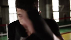 Dark haired young man punching in black boxing bandages and looking seriously at camera in the gym. Close up tired from. Workout boxer. Strength. strong body stock video footage