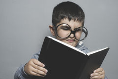 Dark-haired young student reading a funny book, reading and lear Royalty Free Stock Photo