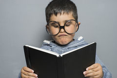 Dark-haired young student reading a funny book, reading and lear Stock Image