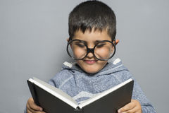 Dark-haired young student reading a funny book, reading and lear Royalty Free Stock Image