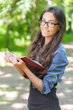 Dark-haired young woman with book Royalty Free Stock Images
