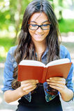 Dark-haired young woman reads red Stock Photo