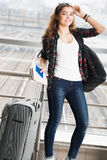 Dark-haired young woman standing with a suitcase and a backpack and holding a passport with a ticket. Full length. Stock Photos
