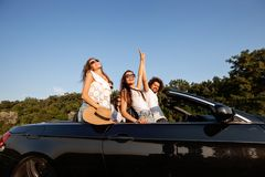 Dark-haired young women and curly dark-haired young man are standing in a black cabriolet on a summer day. stock photo