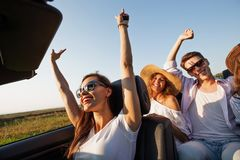 Dark-haired young woman dressed in a white t-shirt is sitting a black cabriolet with friends on a summer day. royalty free stock photography