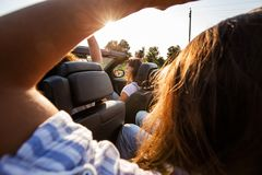 Dark-haired young women is sitting a black cabriolet with friends on a summer day. stock photography