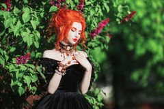 Dark halloween attire. Goth woman with pale skin and red hair in black edwardian gown and renaissance bracelet on hand. royalty free stock images