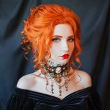 Dark halloween attire. Gothic woman vampire with pale skin and red hair in black dress and baroque necklace on neck. Girl witch with red lips. Gothic look stock photos