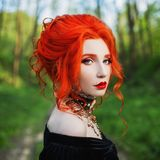 Dark halloween attire. Gothic woman is vampire with pale skin and red hair in a black dress and necklace on neck. Girl witch. With red lips. Gothic attire royalty free stock images