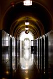 Dark hallway. Long dark hallway with lights reflecting on part of the floor and walls Royalty Free Stock Photography