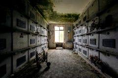 Dark Hallway Leading to Crypts & Coffins - Abandoned Mausoleum. A moody, dark hallway leads to coffins and plaques inside a long abandoned mausoleum stock photo