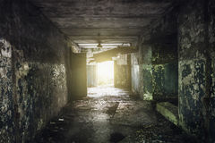 Dark hallway with peeling paint on the walls in an abandoned building Stock Photo
