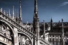 Dark HDR photo of the marble statues and decorations on the Cathedral Duomo di Milano on piazza in Milan and Royal Palace of Milan Stock Image
