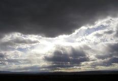 Dark Heavens. Brilliant light shines through dark clouds over the plains of Nevada Stock Photos