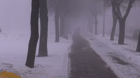 Dark heavy morning fog in snowy street stock video