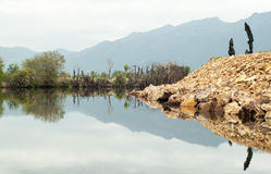 Dark hills reflecting in the lake water Stock Images