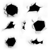 Dark holes. Closeup of a dark holes on white paper set royalty free stock photos
