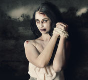 Dark horror scene of an evil zombie woman tied up. Dark horror scene of an evil zombie woman with hands bound and tied, haunted grunge landscape background Stock Photo