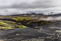 Dark Iceland landscape with green moss and black road, Iceland stock image