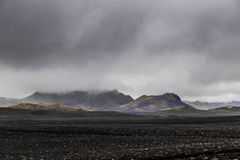 Dark Iceland landscape with green moss and black road, Iceland Royalty Free Stock Images