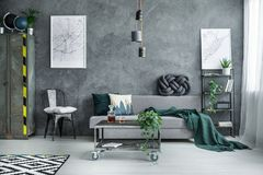 Dark industrial living room. White pillow on black chair between metal wardrobe and grey sofa in dark industrial living room with city map on the wall royalty free stock images