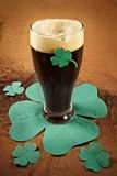 Dark Irish beer for St Patick's Day. On napkins stylized under clover leaf Royalty Free Stock Image
